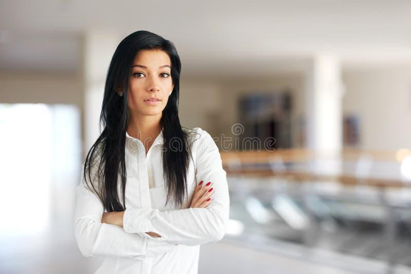 Donna in camicia bianca che sta con le armi attraversate immagini stock