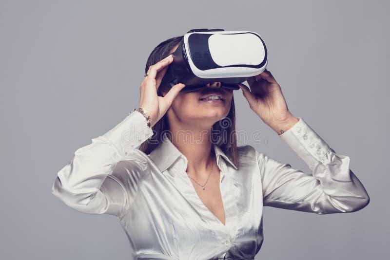 Donna in camicia bianca facendo uso dei vetri del vr immagine stock libera da diritti