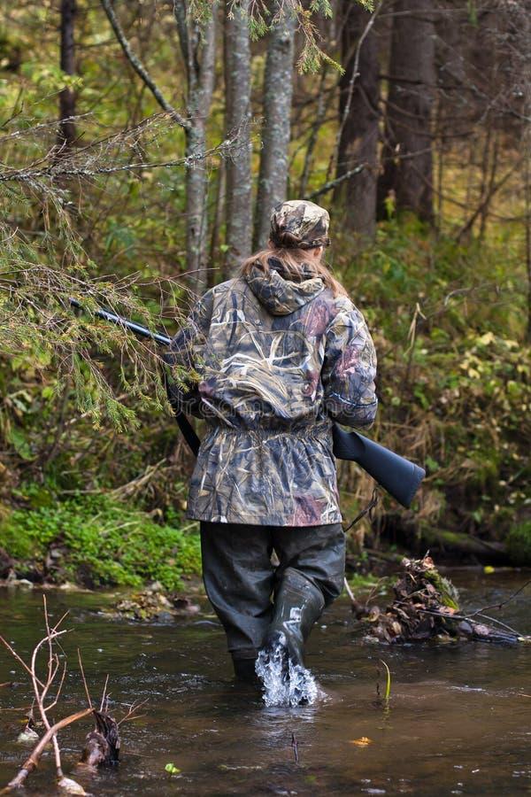 Donna in cammuffamento che attraversa piccolo fiume sulla caccia fotografia stock