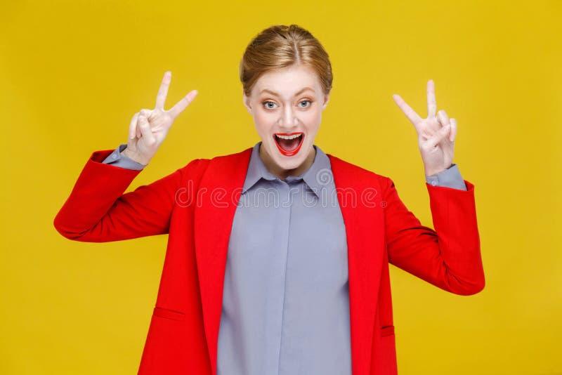 Donna capa di affari di rosso in vestito rosso che mostra il segno di v, pace, quattro s fotografia stock libera da diritti