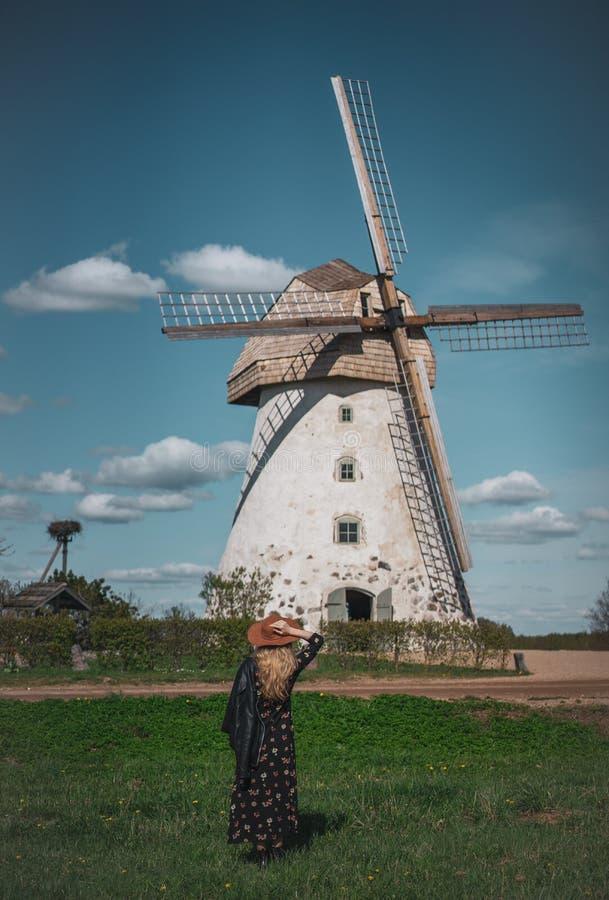 Donna in cappello che esamina la vecchia costruzione del wildmill, giorno soleggiato di estate fotografia stock
