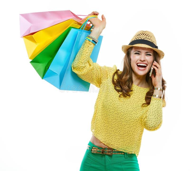Donna in cappello con i sacchetti della spesa che parla telefono cellulare e che si rallegra fotografie stock