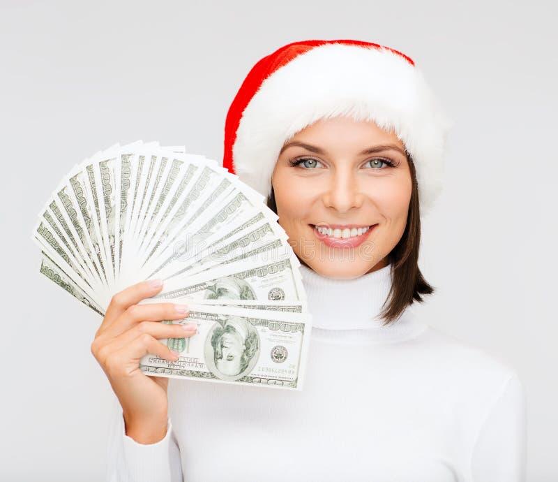 Donna in cappello dell'assistente di Santa con i soldi del dollaro americano fotografia stock