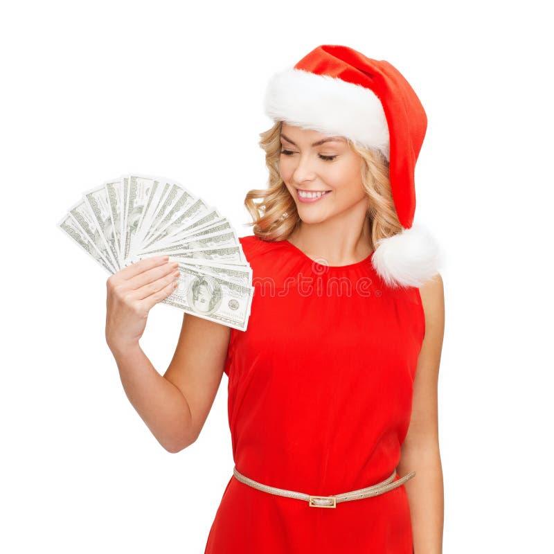 Donna in cappello dell'assistente di Santa con i soldi del dollaro americano fotografia stock libera da diritti