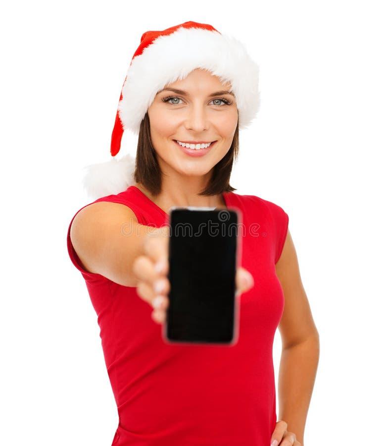 Donna in cappello dell'assistente di Santa con lo smartphone fotografia stock