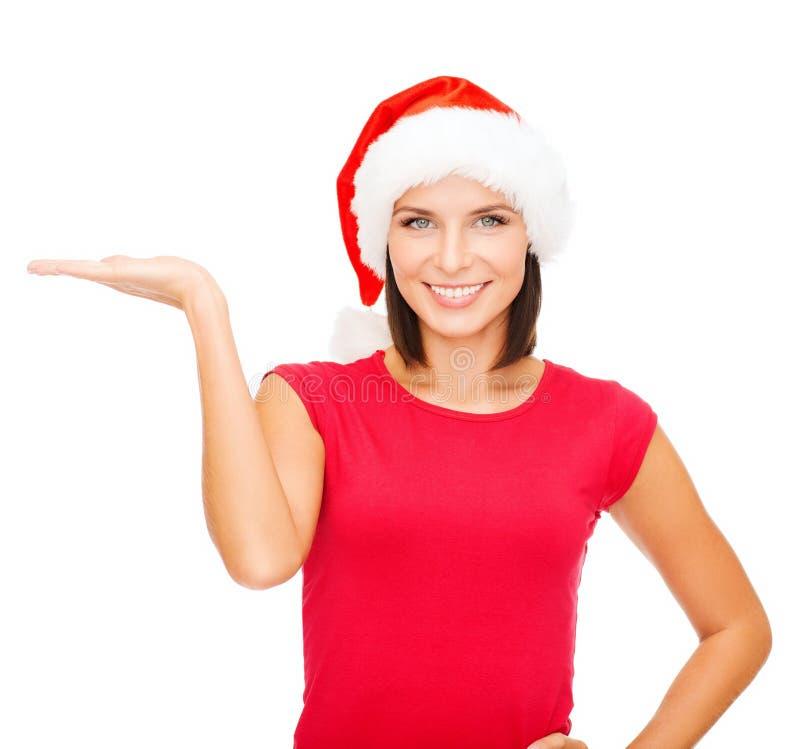 Donna in cappello dell'assistente di Santa con qualcosa sulla palma immagini stock