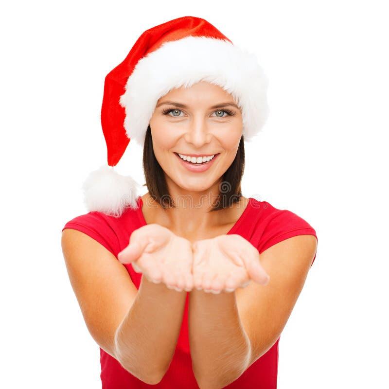 Donna in cappello dell'assistente di Santa con qualcosa sulle palme immagini stock