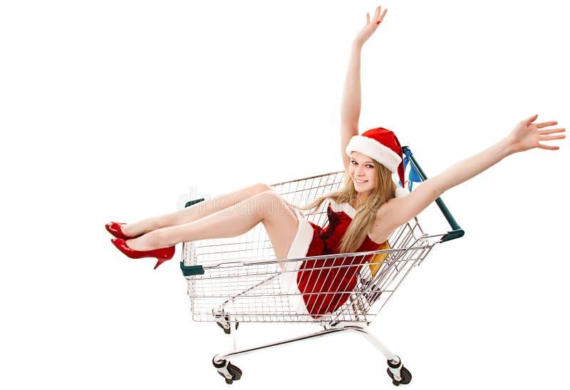 Donna in cappello della Santa che si siede in carrello di acquisto immagini stock