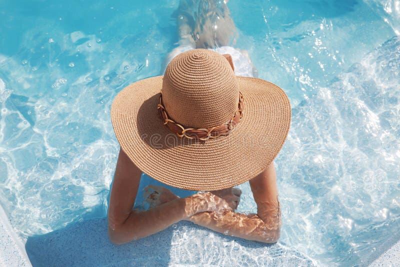 Donna in cappello della spiaggia che gode nella piscina su tropicale di lusso immagine stock