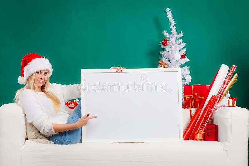 Donna in cappello di Santa che tiene bordo in bianco bianco immagini stock libere da diritti