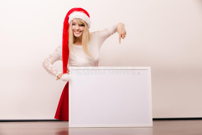 Donna in cappello di Santa con l'insegna in bianco Copi lo spazio fotografia stock libera da diritti