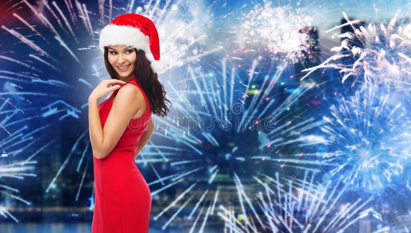 Donna in cappello di Santa e vestito rosso sopra il fuoco d'artificio immagine stock libera da diritti