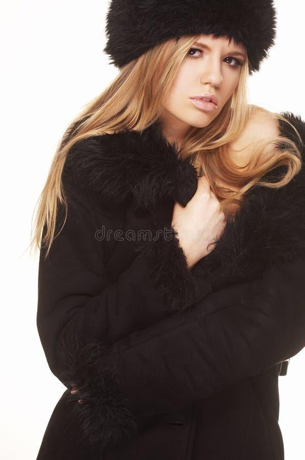 Donna in cappello e cappotto di pelliccia neri fotografia stock libera da diritti