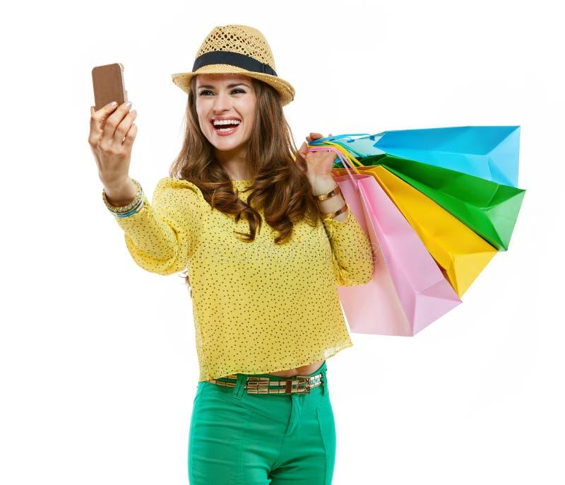 Donna in cappello e vestiti luminosi con i sacchetti della spesa che prendono selfie immagine stock libera da diritti