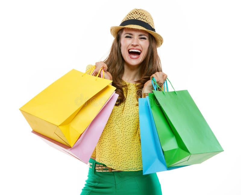 Donna in cappello e vestiti luminosi con i sacchetti della spesa che si rallegra immagini stock libere da diritti