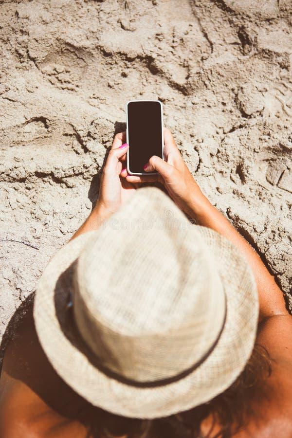 Donna in cappello facendo uso del telefono cellulare sulla spiaggia fotografie stock
