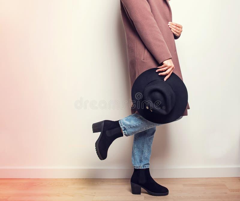 Donna in cappotto beige ed in stivali alla moda che giudicano un cappello disponibile fotografie stock