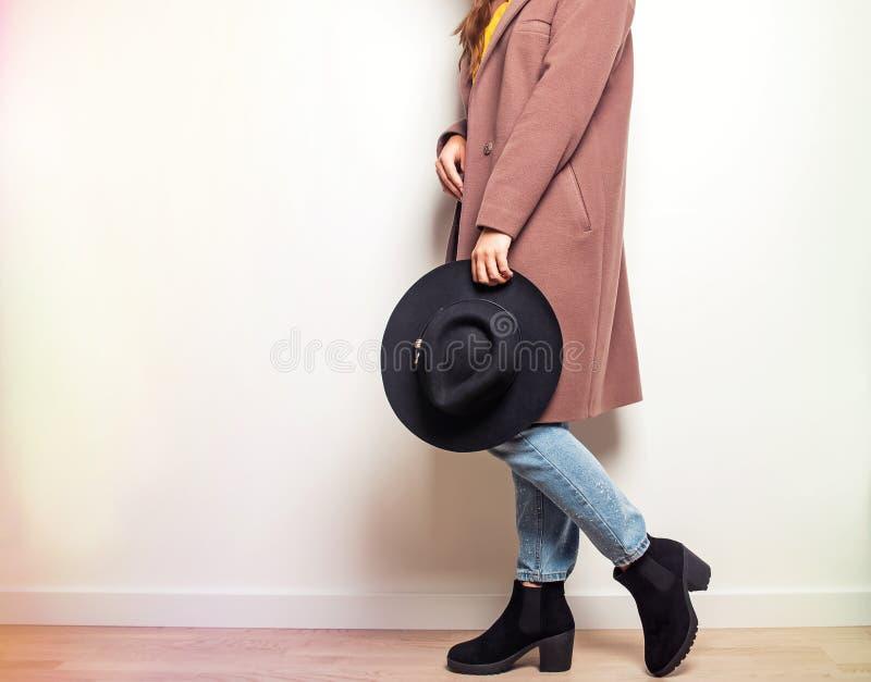 Donna in cappotto beige ed in stivali alla moda che giudicano un cappello disponibile immagini stock