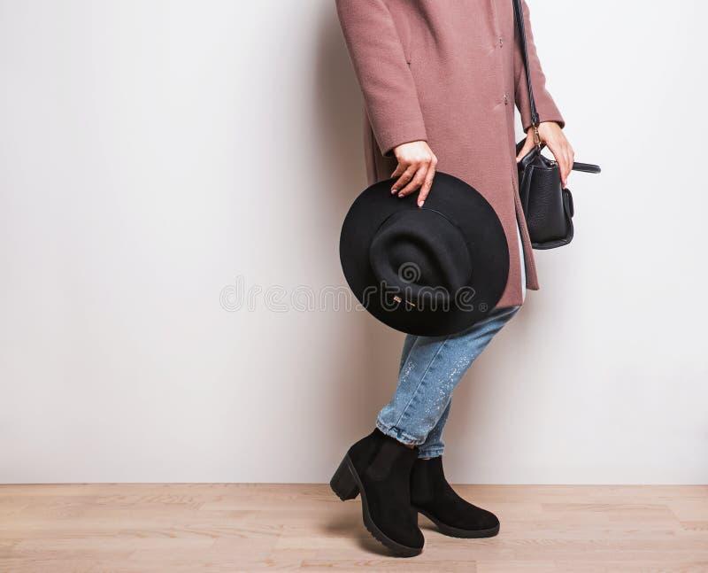 Donna in cappotto beige ed in stivali alla moda che giudicano un cappello disponibile fotografia stock libera da diritti