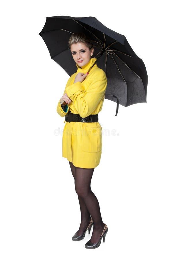 Donna in cappotto, pattini ed ombrello gialli fotografie stock