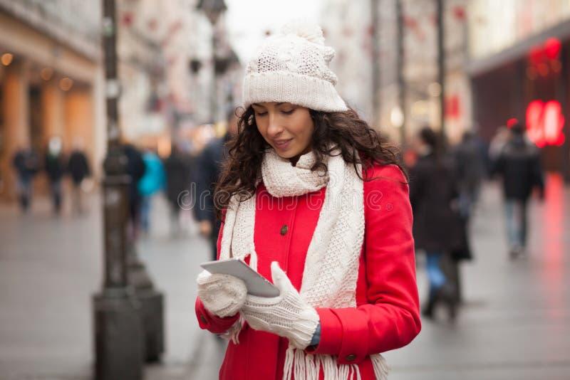 Donna in cappuccio rosso della lana e del cappotto e guanti con lo smartphone in Han fotografia stock