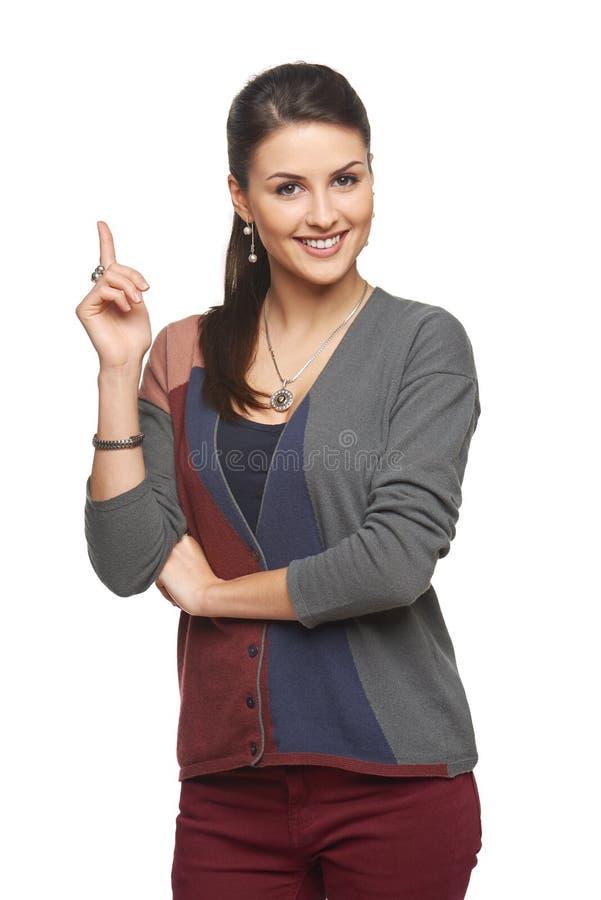 Donna in cardigan che indica allo spazio in bianco della copia fotografia stock libera da diritti