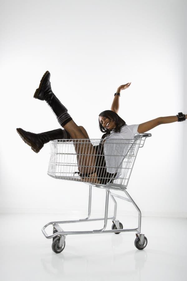 Donna in carrello di acquisto. fotografia stock