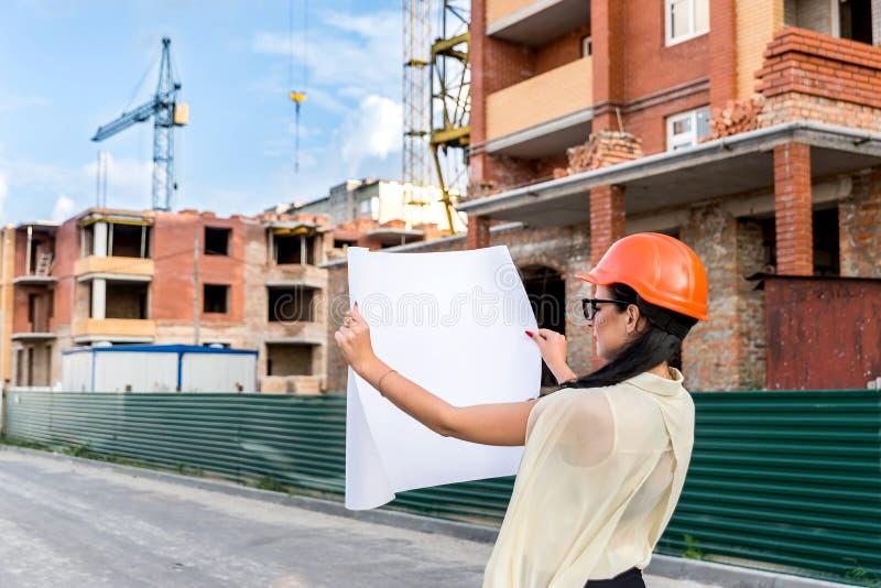 Donna in casco che esamina disegno il cantiere fotografie stock libere da diritti