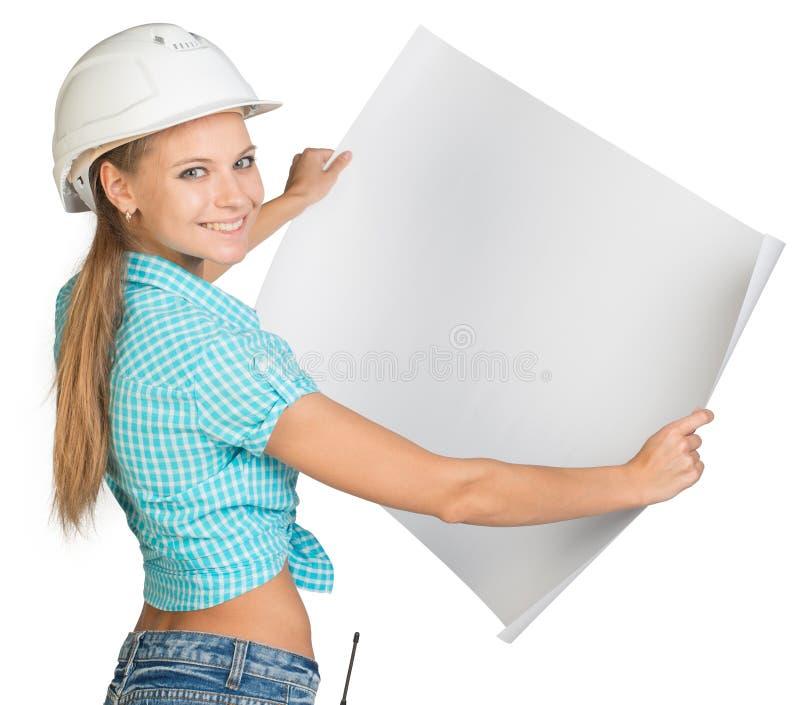 Donna in casco che mostra foglio bianco del disegno immagini stock libere da diritti