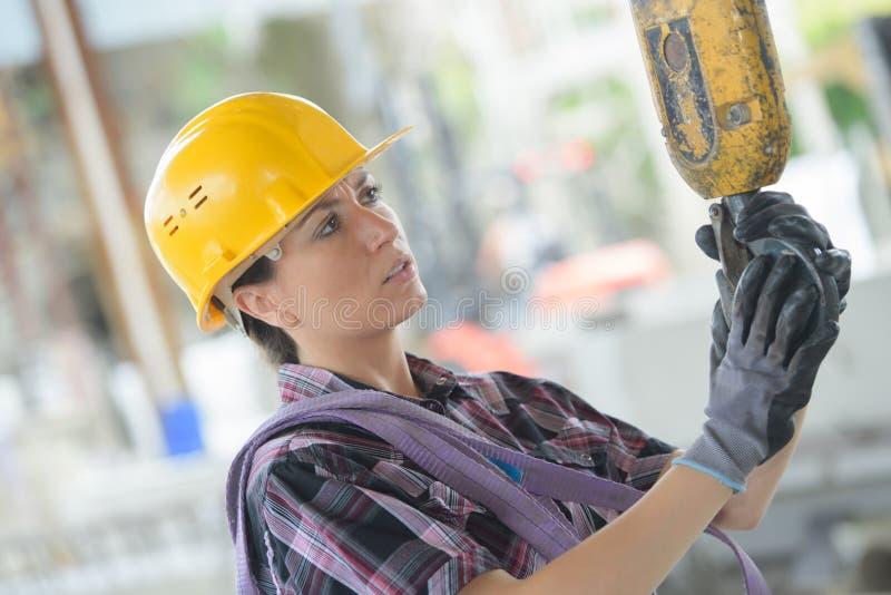 Donna in casco giallo che lavora al cantiere immagine stock libera da diritti