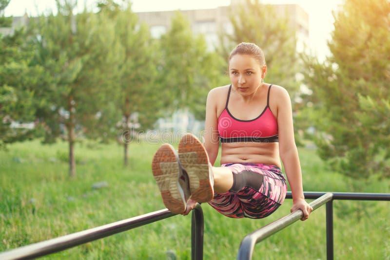 Donna castana adatta che fa esercitazione per i suoi muscoli addominali immagine stock