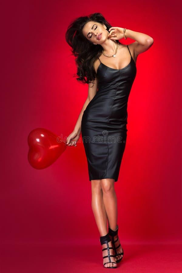 Donna castana adorabile con il pallone del cuore fotografia stock