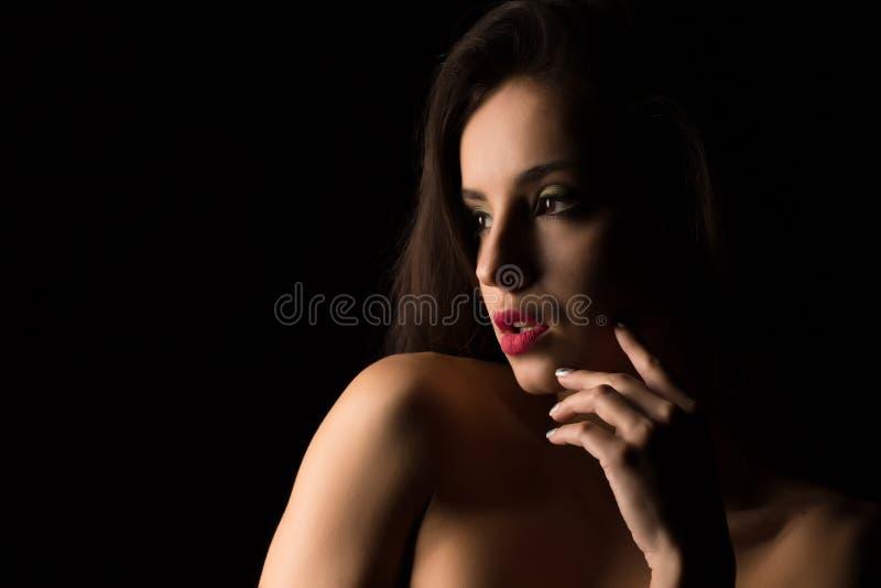 Donna castana alla moda con trucco luminoso che posa con nudo fotografia stock