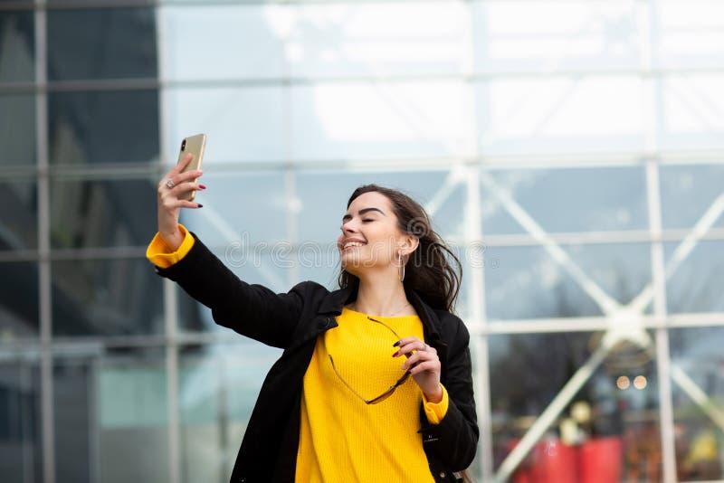 Donna castana allegra in maglione giallo che fa sefie contro il fondo dell'aeroporto Tecnologia moderna immagini stock libere da diritti