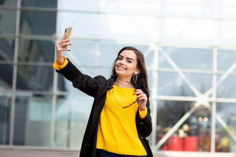 Donna castana allegra in maglione giallo che fa sefie contro il fondo dell'aeroporto Tecnologia moderna fotografie stock