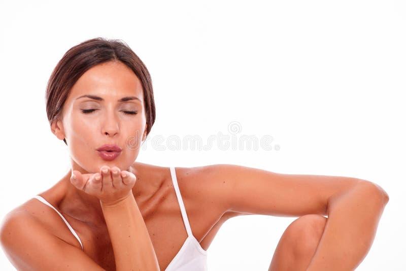 Donna castana attraente che soffia un bacio fotografia stock libera da diritti