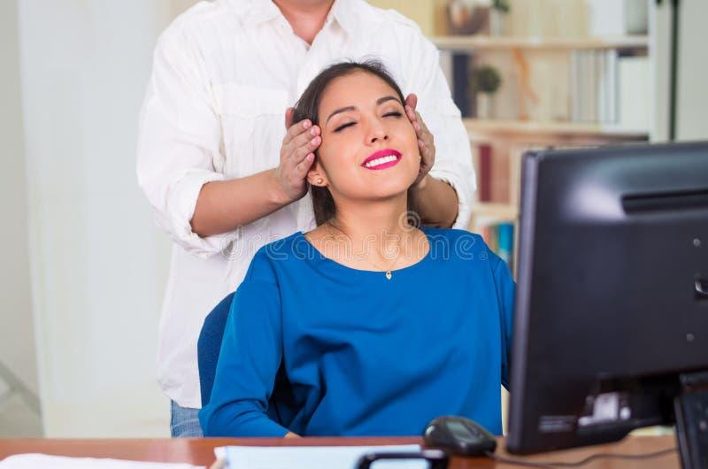 Donna castana attraente dell'ufficio che porta maglione blu che si siede dallo scrittorio che riceve massaggio capo, concetto di  immagine stock
