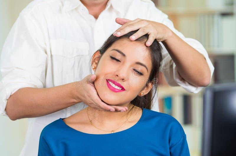 Donna castana attraente dell'ufficio che porta maglione blu che si siede dallo scrittorio che riceve massaggio capo, concetto di  immagini stock