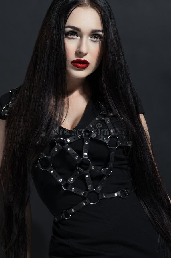 Donna castana attraente in vestito nero fotografia stock libera da diritti