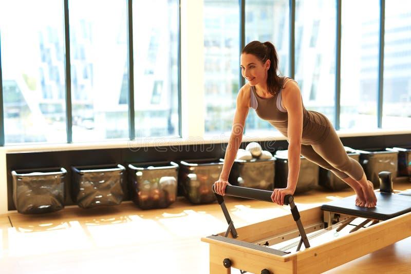 Donna castana che pratica Pilates in studio fotografia stock libera da diritti