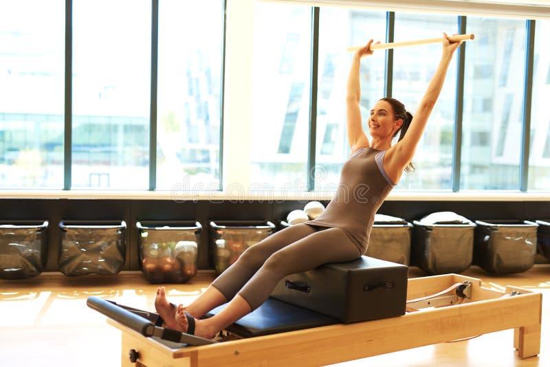 Donna castana che pratica Pilates in studio fotografia stock