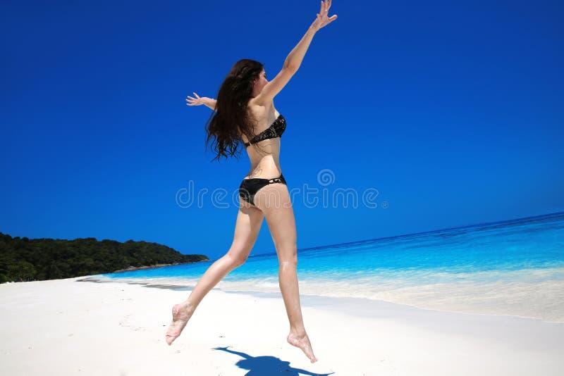 Donna castana che salta sulla spiaggia tropicale Vacanza di estate felice immagini stock