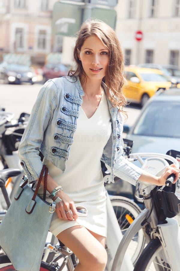 Donna castana che si siede sulla bicicletta vicino al parcheggio della bici immagine stock
