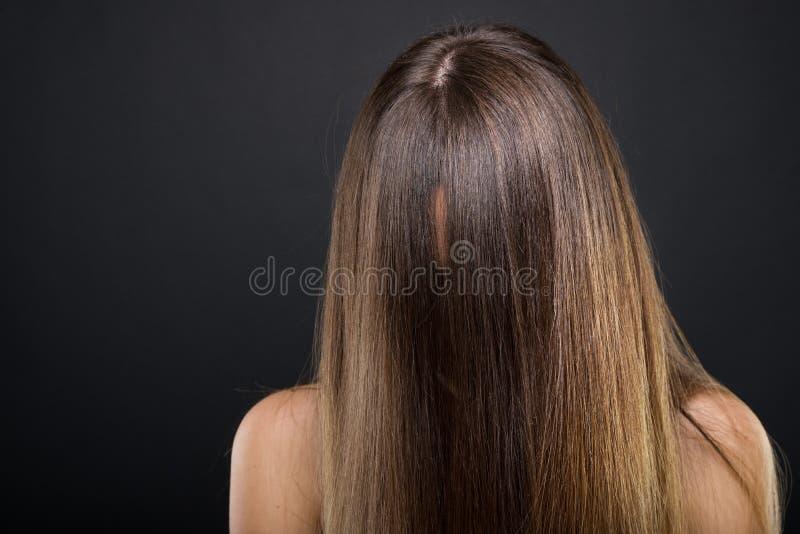 Donna castana con capelli lunghi che coprono il suo fronte fotografie stock libere da diritti