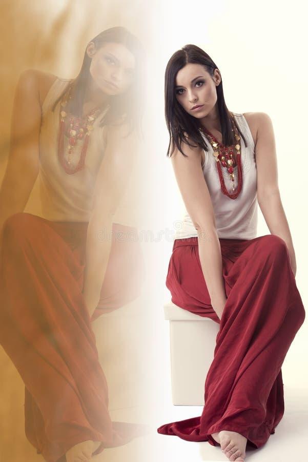 Donna castana con la camicia bianca, lungamente gonna rossa e gioielli, sedentesi in una posa sopra bianco, con la riflessione immagini stock