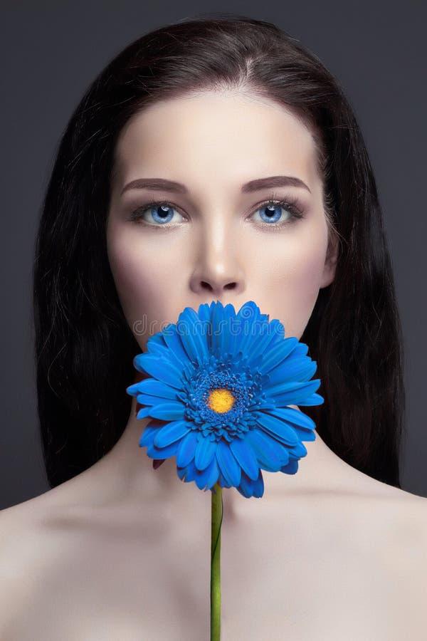 Donna castana contro un fondo scuro, fiore blu del ritratto a disposizione Cura di capelli e pelle, trucco professionale Brigh mi fotografia stock