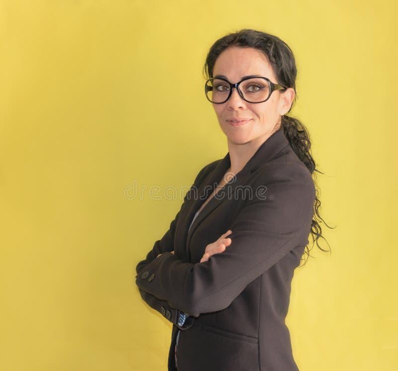 Donna castana di affari con i vetri che sorride alla macchina fotografica immagini stock