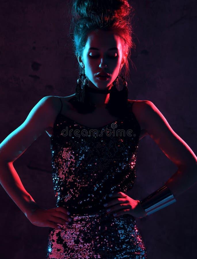 Donna castana di bello modo che posa alla luce al neon blu e rosa in vestito dalla scintilla dell'oro di modo su buio fotografia stock libera da diritti