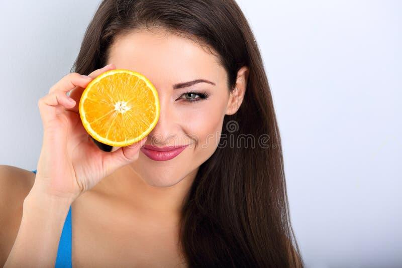 Donna castana di bello trucco che tiene frutta arancio fresca vicino immagini stock