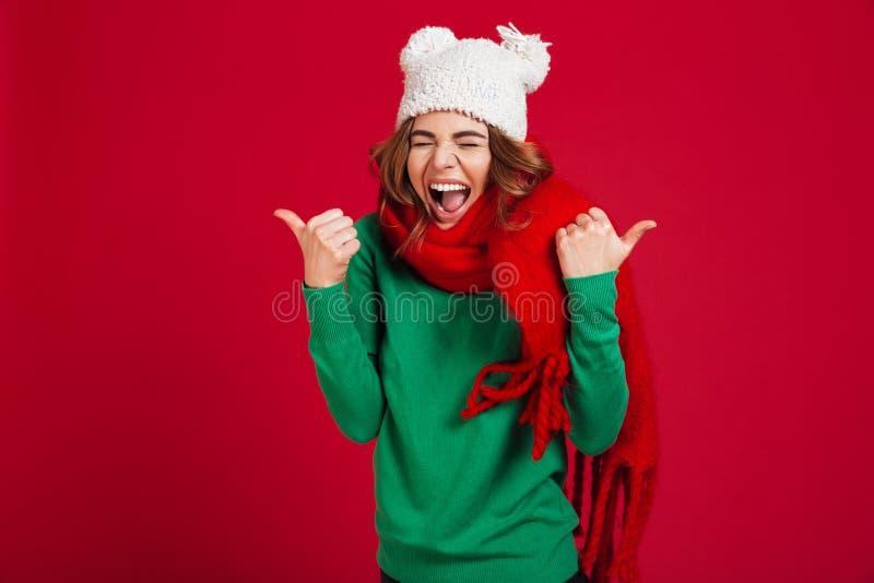 Donna castana di grido felice in maglione, cappello divertente e sciarpa fotografia stock